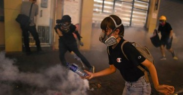 Protesters run away after police fired tear gas shells in the Sham Shui Po Area of Hong Kong on August 14, 2019.