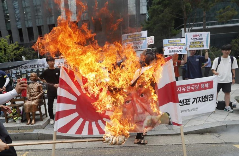 South Korean college students burn a banner showing an image of a Japanese rising sun flag and Japanese Prime Minister Shinzo Abe during a rally denouncing the Japanese government's decision on their exports to South Korea in front of the Japanese embassy in Seoul.