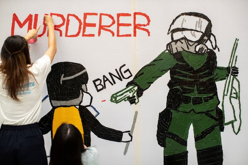 Anti-government protesters make a mural depicting the student protester who got shot by police.